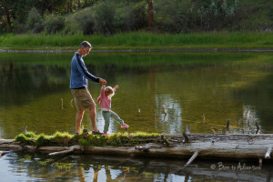 child walking the log with her dad